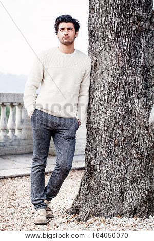 Handsome young man alone in nature near a tree outdoors. A charming and handsome young man leaning on a tree trunk. His gaze is directed upward with his hands in his pockets. He dressing gowns autumn or winter. White sweater and gray trousers.