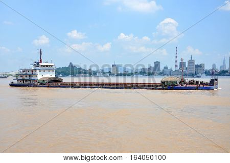 Barge on Yangtze River, with the Nanjing skyline on the background, Nanjing, Jiangsu Province, China.