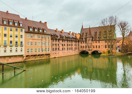 Nuremberg, Germany - December 24, 2016: Old buildings and arch bridge reflected in water in Nuremberg, Bavaria