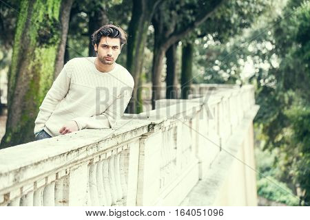 Charming young and handsome man with stylish hair and white sweater waiting leaning on a low terrace wall. Handsome serene young man model leaning on a wall of a terrace, trees park. Outdoors in a park with a series of trees. Peaceful and calm attitude.