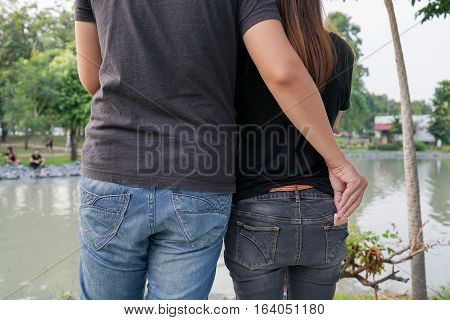 Man pretend to hug a woman for stealing smart phone from behind pocket on jeans at park