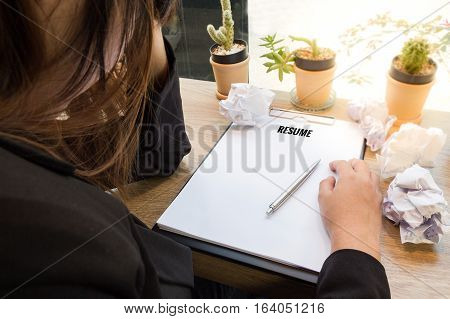 Stressed businesswoman writing resume on paper at wooden desk with paper balls.