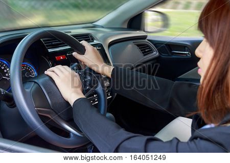 Woman driving a car and pressing on horn button - transportation concept