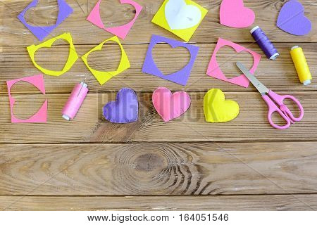 Valentine's day hearts crafts. Colorful hearts gifts made of felt, felt scraps, scissors, thread on wooden table. Valentine's day handmade gifts concept. Needlework background. Top view