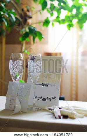 Wine glasses wedding card with ribbons and an invitation to the table window and flowers in the background