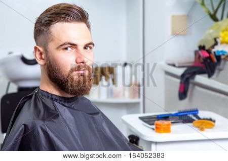 happy stylish man in a barber shop looking at camera after working.