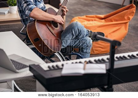 Enjoying every second. Devoted stylish incapacitated person dedicating his leisure time to songwriting using his guitar while spending time in his apartment