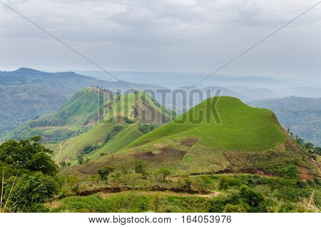 Rolling fertile hills with fields and crops on Ring Road of Cameroon, Africa.