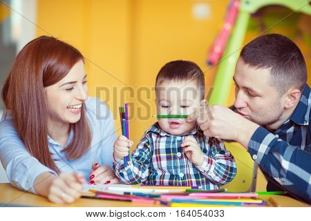 Young Happy Family With Toddler Boy Playing Together At Home