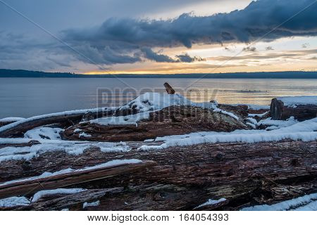 Snow covers driftwood on shore of the Puget Sound in Washington State.