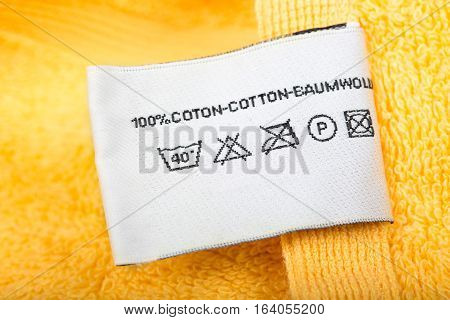 Clothing label with laundry care instructions closeup cloth label on yellow cloth