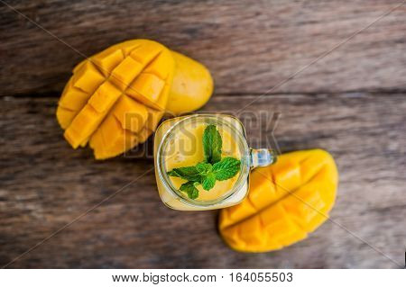 Mango Smoothie In A Glass Mason Jar And Mango On The Old Wooden Background. Mango Shake.