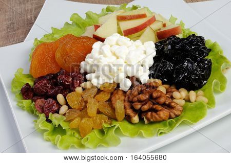 Vitamin salad with nuts apples dried fruit and cottage cheese in lettuce leaves