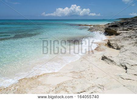 Small waves hitting rocky beach on uninhabited island Half Moon Cay (The Bahamas).