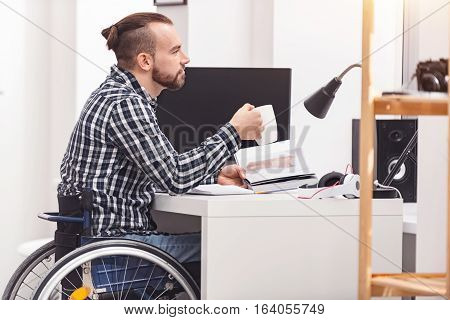A lot to do today. Attractive concentrated disabled guy considering new ideas while sitting at his workplace and holding an open book in his hands