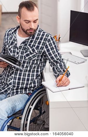 Writing down the important. Attractive smart disabled guy outlining some essentials point of the book while holding it in his hand and sitting in his wheelchair at the table