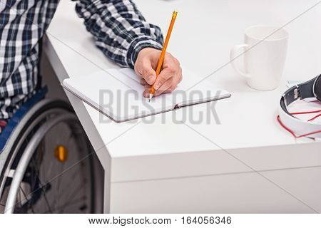 Fresh start. Stylish young handicapped man trying writing something down in a fresh notebook using a pencil while sitting at the table in a wheelchair
