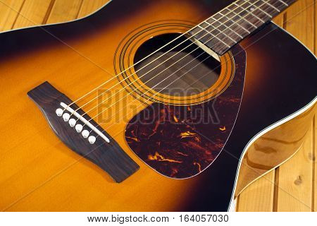 Fragment of six strings acoustic guitar with sunburst color on wooden background top closeup