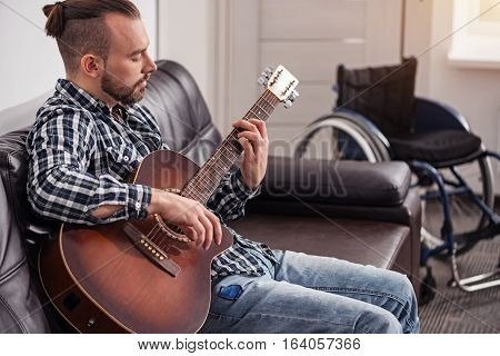 A bit of music. Talented attractive committed guy playing guitar while sitting in a sofa at the living room spending his weekend at home