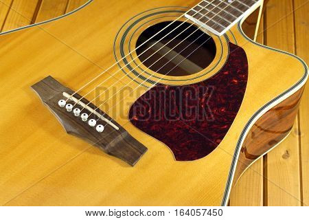 Classic acoustic guitar natural color top fragment with six strings on wooden background closeup