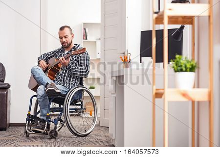Feeling the melody. Inspired disabled young gentleman enjoying guitar playing while sitting in his wheel chair and spending his weekend at home