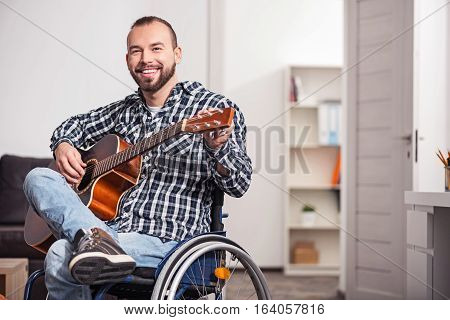 Improving the quality. Pleasant smiling enthusiastic man making the sound of his guitar better while spending his time in the living room sitting in a wheelchair