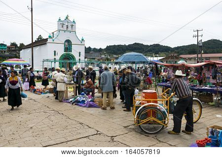 San Juan Chamula Mexico - May 11 2014: Local people in a market in front of the Church of San Juan in the town of San Juan Chamula Chiapas Mexico