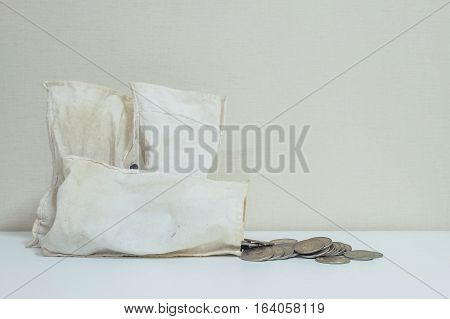 Closeup coin with old white money bag on the table and wallpaper in room textured background with copy space