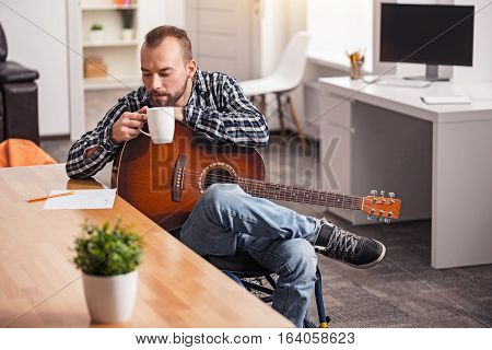 Looking pretty nice. Focused handsome disabled man perusing lyrics of his song while sipping coffee from the cup he holding and sitting at the table