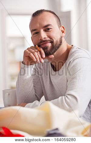 Enthusiastic talented good looking guy holding a pencil and sitting at the table while posing for a photographer in his home studio.
