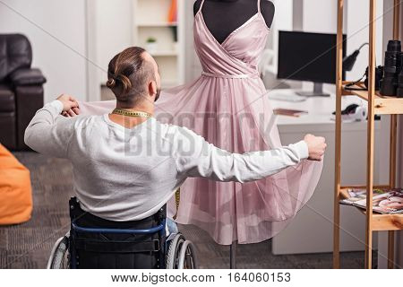 Good job. Demanding professional disabled designer checking finished dress and enjoying his work while spending time at home