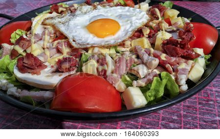 Plate of fried egg chunks of bacon sausage cheese served with red tomato and lettuce