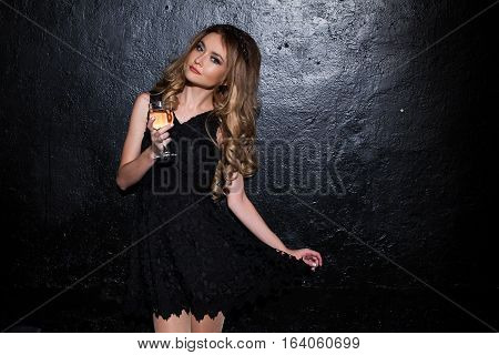 the girl against the wall in a black cocktail dress
