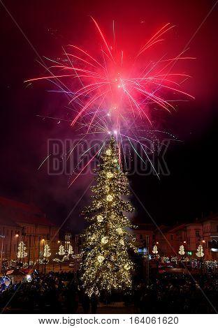 New Year`s Eve firework behind Christmas tree. Celebrating 2017 in Banska Bystrica, Slovakia. Multicolor explosion on dark sky. Foundation day of Slovak republic