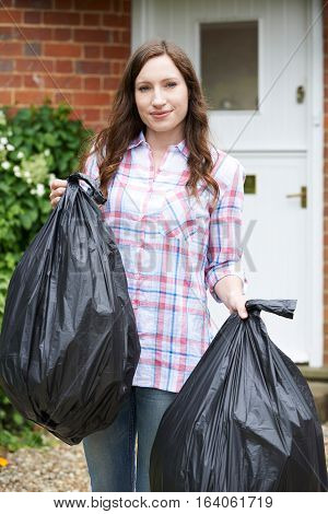 Portrait Of Woman Taking Out Garbage In Bags