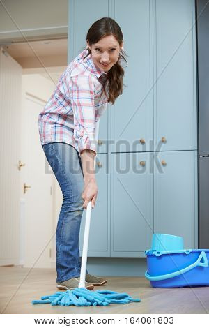 Portrait Of Woman Cleaning Kitchen Floor With Mop