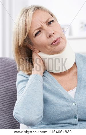 Mature Woman Wearing Surgical Collar In Pain