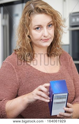 Concerned Plus Size Female Reading Nutritional Information On Packet