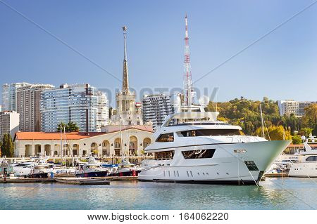 Sochi sea port view from water. Luxury yachts and private boats moored at pier. In background architecture modern resort town hotels and sanatoriums. Marine station complex Port. Krasnodarskiy Russia