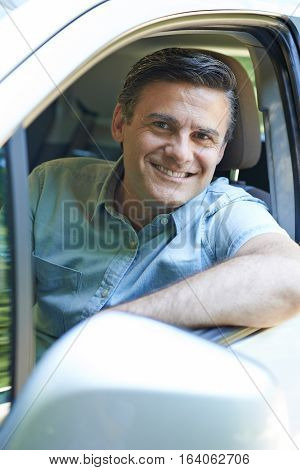 Portrait Of Smiling Mature Man Driving Car