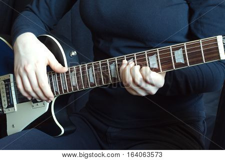 Musician in black on a black six strings electric guitar playing. Hands of the musician closeup