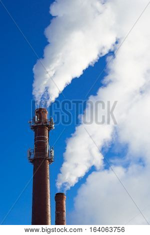 High brick chimney heating boiler house clubs up smoke on blue sky background. Winter Sunny day in large industrial city. Heating season in cold time of year