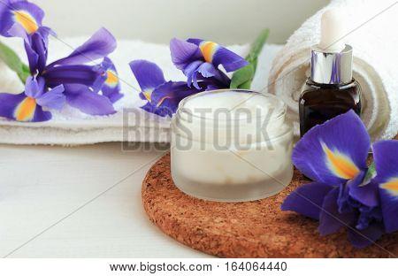 Herb-infused facial mask white jar, fresh iris flowers, aroma bottle. Botanical skincare.