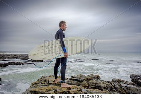 A male surfer with wetsuit and surfboard under arm stands on the rocks and view the surf conditions before entering the water.