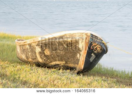 The hull of an old boat lies on the grass by the river.
