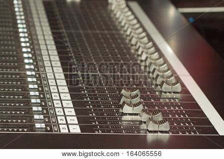 Big multichannel audio sound mixer with many buttons and sliders. Closeup view