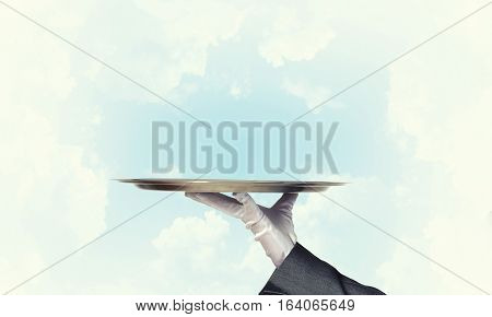 Butler hand in white glove presenting empty tray