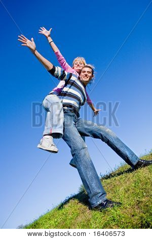 Happy young couple  jumping in sky above a green meadow