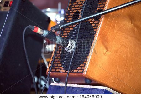 Sound amplifying equipment: microphone and mid size sound speaker system in brown wooden cabinet on concert stage. Closeup view