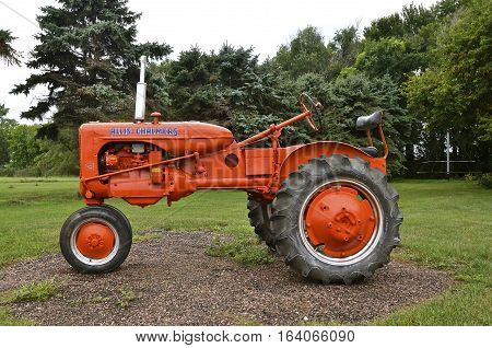 MADISON, SOUTH DAKOTA: August 20, 2016:  The  restored orange tractor is an Allis Chalmers C, a U.S. manufacturer of machinery for various industries includung agricultural equipment, construction, power generation, and power transmission.